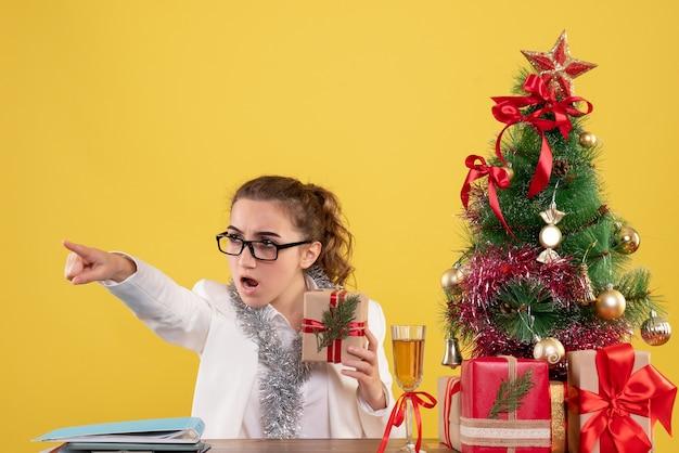Médica vista frontal sentada com presentes de natal e árvore apontando no fundo amarelo