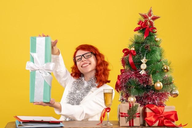 Médica vista frontal sentada com presentes de natal e árvore em fundo amarelo