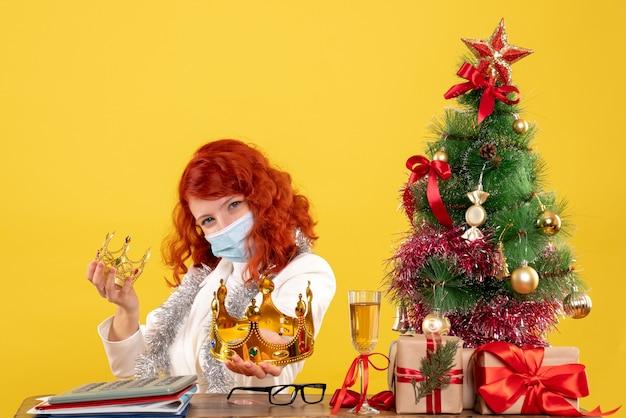 Médica vista frontal sentada com presentes de natal e segurando coroas em fundo amarelo