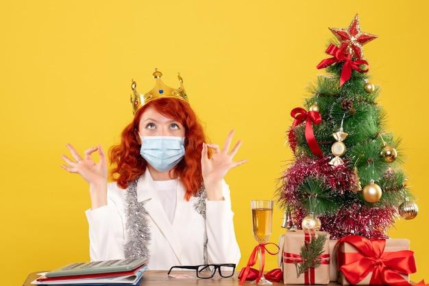 Médica vista frontal sentada com presentes de natal e usando coroa sobre fundo amarelo