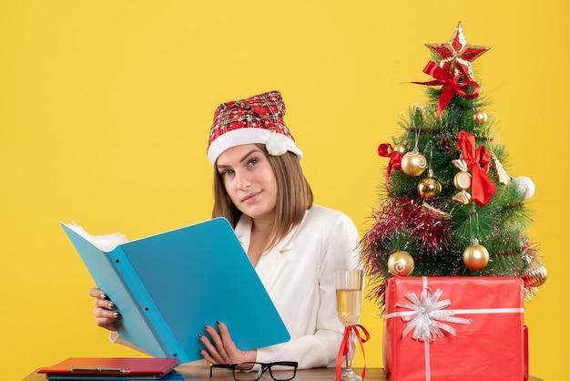 Médica vista frontal sentada com presentes de natal segurando arquivos em fundo amarelo
