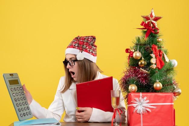 Médica vista frontal sentada com presentes de natal segurando uma calculadora em fundo amarelo
