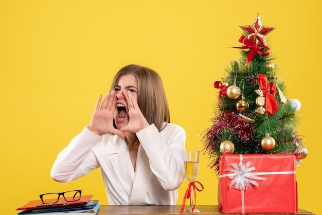Médica vista frontal sentada em frente à mesa chamando em voz alta sobre fundo amarelo com árvore de natal e caixas de presente