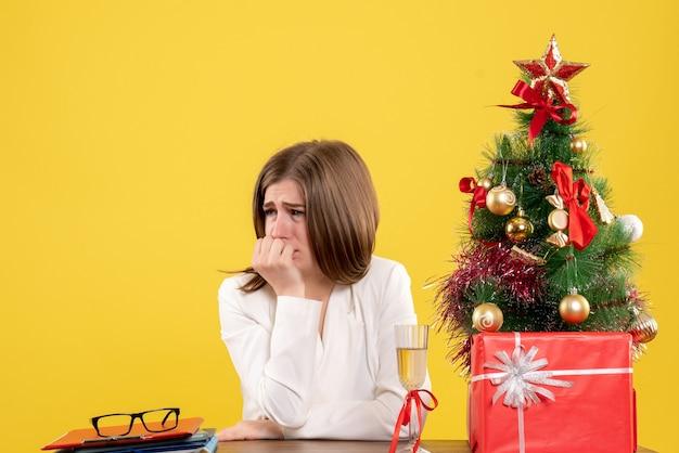 Médica vista frontal sentada em frente à mesa, chorando sobre fundo amarelo com árvore de natal e caixas de presente
