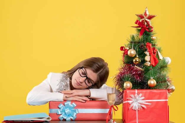 Médica vista frontal sentada em frente à mesa com presentes e árvore dormindo em fundo amarelo com árvore de natal e caixas de presente