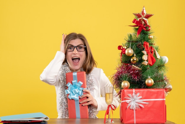 Médica vista frontal sentada em frente à mesa com presentes e árvore em fundo amarelo com árvore de natal e caixas de presente