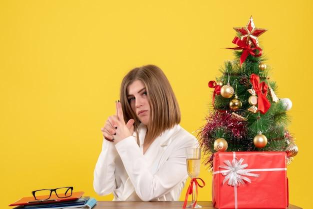 Médica vista frontal sentada em frente à sua mesa em um fundo amarelo com árvore de natal e caixas de presente