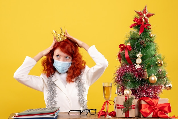 Médica vista frontal sentada na máscara com presentes de natal usando coroa sobre fundo amarelo