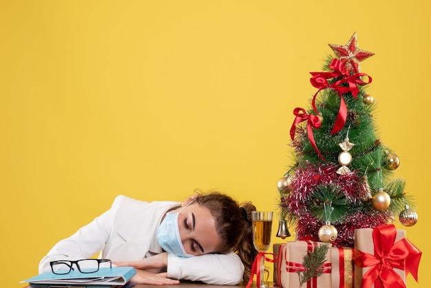 Médica vista frontal sentada na máscara protetora dormindo sobre fundo amarelo com árvore de natal e caixas de presente