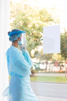 Médica vista lateral olhando pela janela