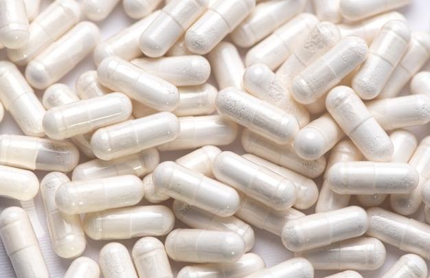 Medicação. comprimidos brancos com pó branco em nutri em um fundo branco