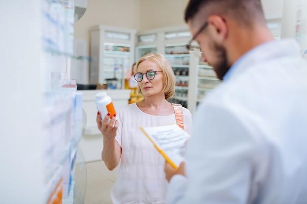 Medicamento certificado. cliente maduro sério usando óculos, segurando um frasco com vitaminas