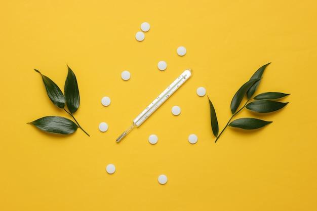 Medicamento fitoterápico termômetro de comprimidos brancos com folhas verdes sobre fundo amarelo