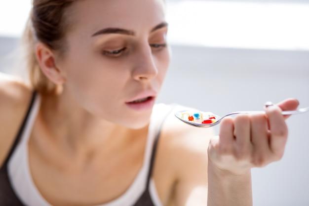 Medicamento forte. foco seletivo de comprimidos tomados por uma mulher doente e infeliz