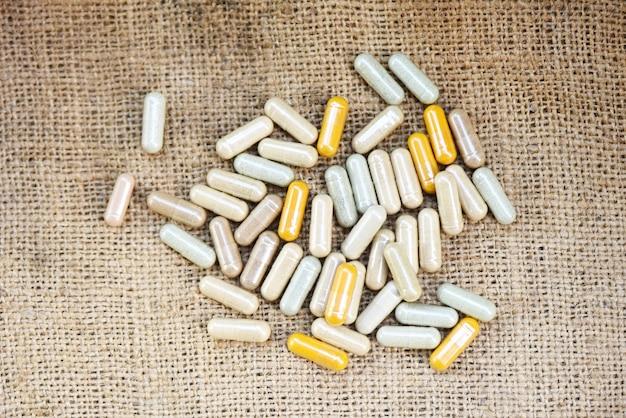 Medicamentos à base de plantas - cápsulas de ervas naturais em fundo de saco, foco seletivo de vista superior