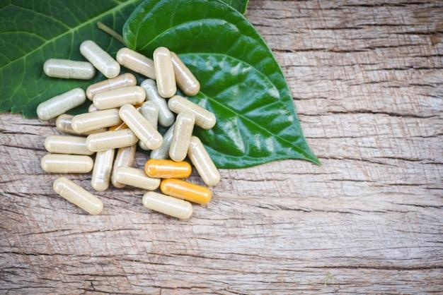 Medicamentos à base de plantas / cápsulas de ervas naturais na folha verde e fundo rústico