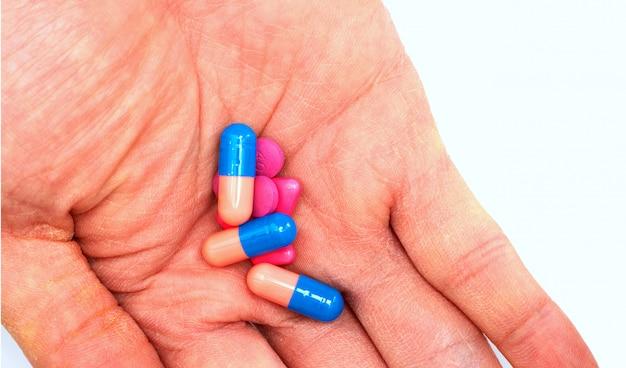 Medicamentos à mão antes de tomar por via oral no conceito de consumo de drogas, fechado