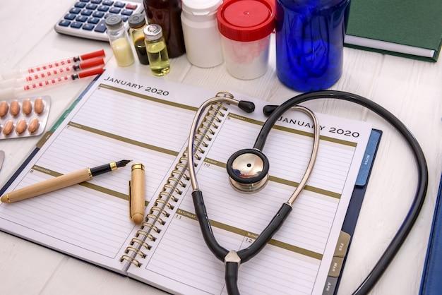 Medicamentos com diário na mesa close-up