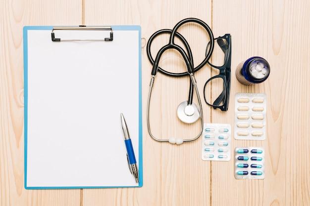 Medicamentos e estetoscópio perto de prancheta e óculos