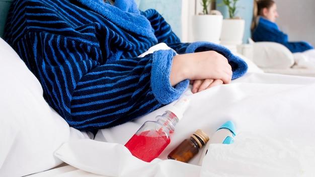 Medicamentos e mulher doente deitada na cama.