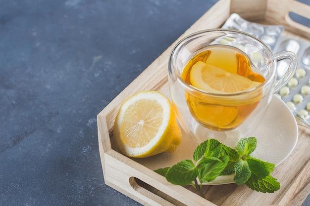 Medicamentos e saúde conceito de saúde. xícara de chá quente com limão, pílulas e termômetro