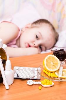 Medicamentos e vitaminas na criança de mesa em uma cama que tem varicela