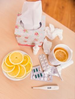 Medicamentos, guardanapos, chá com limão na mesa.
