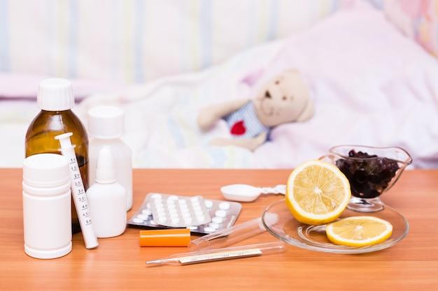 Medicamentos na cama infantil de mesa com um brinquedo macio
