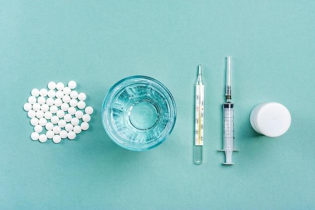 Medicamentos, pílulas, copo de água, termômetro, medicamentos para o tratamento de resfriados, gripe, calor em um fundo cinza.