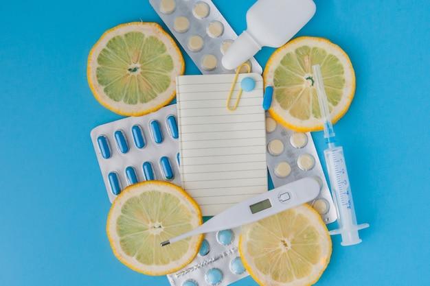 Medicamentos, pílulas, termômetro, medicina tradicional para o tratamento de resfriados, gripe, calor em uma parede azul. manutenção da imunidade. doenças sazonais. vista do topo. lay plana de medicina