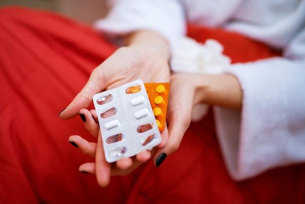 Medicamentos que estão sendo mantidos pela mulher que está coberta no cobertor vermelho.
