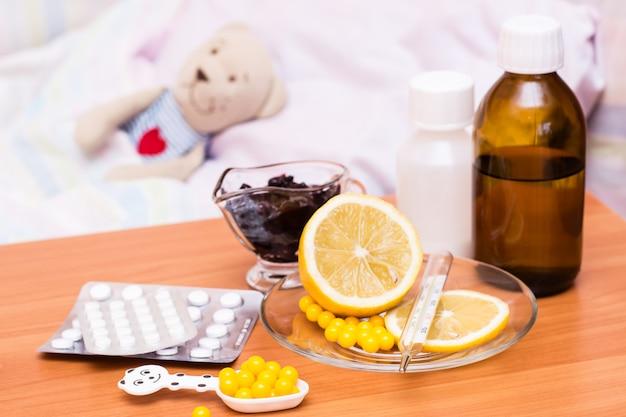 Medicamentos, vitaminas, limão e geléia na cama infantil da mesa com um brinquedo macio
