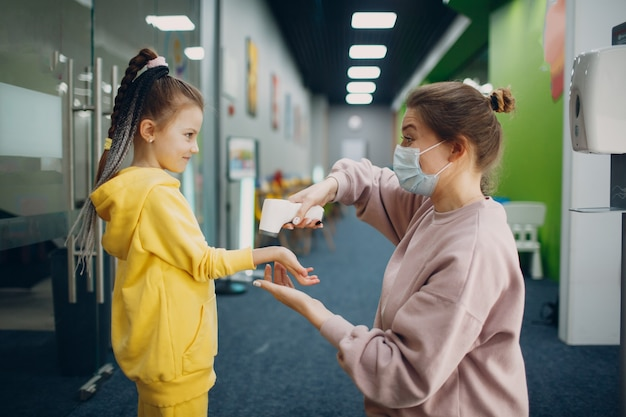 Medição da temperatura das mãos de crianças por termômetro a laser no jardim de infância