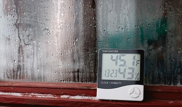 Medição da temperatura do ar, ponto de orvalho, umidade com um dispositivo (higrômetro), contra janela com condensação