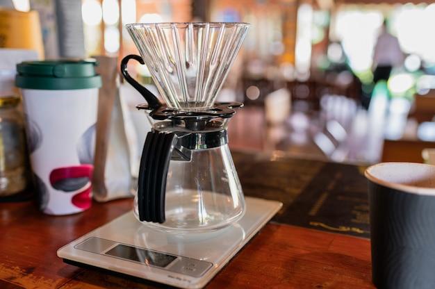 Medição de café por gotejamento com caneca de vidro no balcão