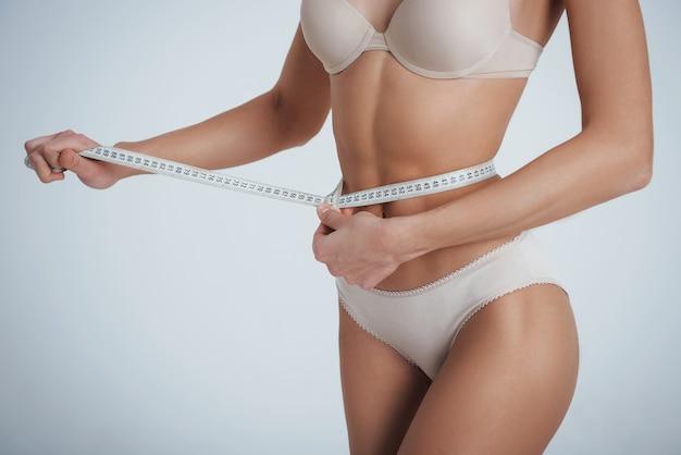 Medição de circunferência. menina na cueca branca com fita métrica em volta da cintura.
