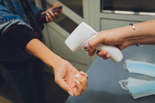 Medição de temperatura por termômetro infravermelho eletrônico da mão de uma mulher na entrada de um