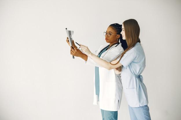 Médicas em roupões de banho. garota africana. estetoscópio no pescoço do médico.