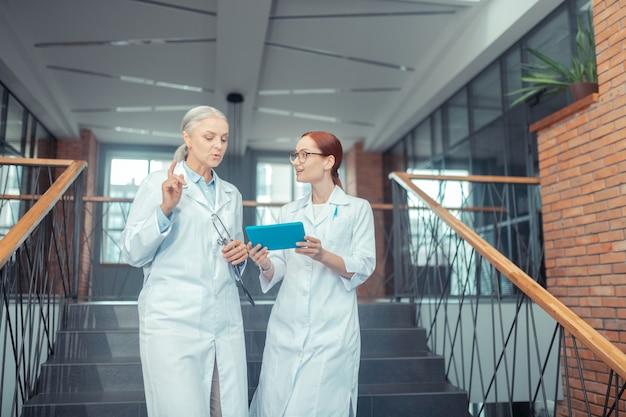 Médicas. médica sênior, branca, em pé na escada de um estabelecimento médico moderno, enquanto conversava com sua jovem colega