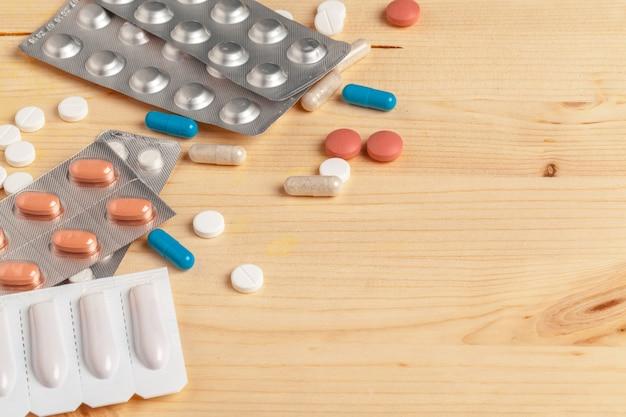 Médicas pílulas coloridas, cápsulas ou suplementos para o tratamento e cuidados de saúde em fundo de madeira