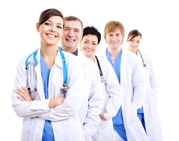 Médicas rindo felizes em batas de hospital enfileiradas