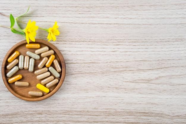 Medicina alternativa à base de plantas em cápsulas na mesa de madeira com espaço de cópia para a formação médica