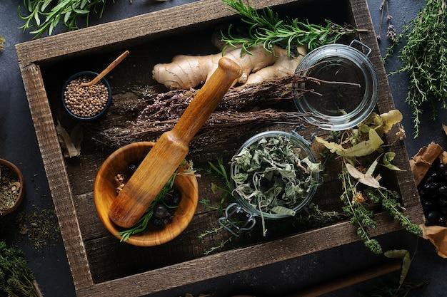 Medicina alternativa, tratamento à base de plantas. argamassa de madeira, hortelã, tília, tomilho, lavanda em um fundo escuro, vista superior.