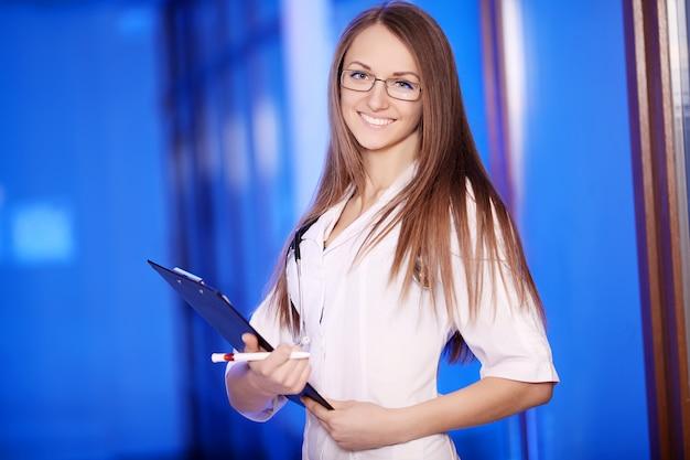 Medicina. atraente médica na frente, mulher azul, bonita, jovem médico, entrelaça