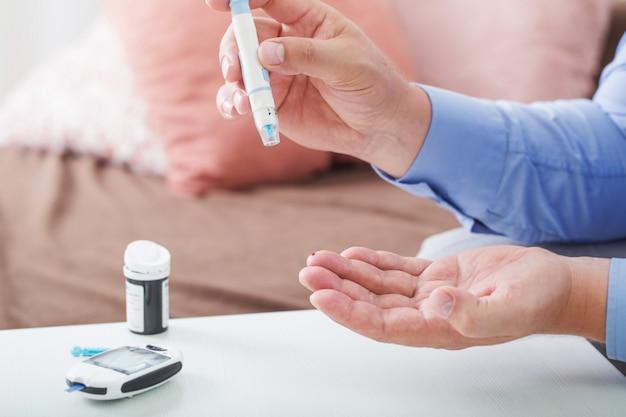 Medicina, diabetes, glicemia, cuidados de saúde e conceito de pessoas. close-up do dedo masculino com tira de teste