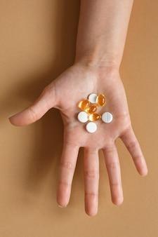 Medicina e saúde. comprimidos e cápsulas com vitaminas na palma da mão de uma mulher. dieta e alimentação saudável