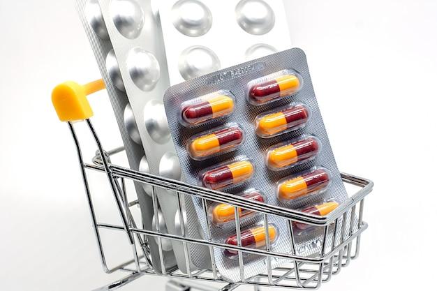 Medicina, pílulas, drogas ou comprimidos em um blister no carrinho de compras em fundo branco