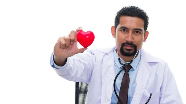 Médico adulto com estetoscópio segurando o coração vermelho.