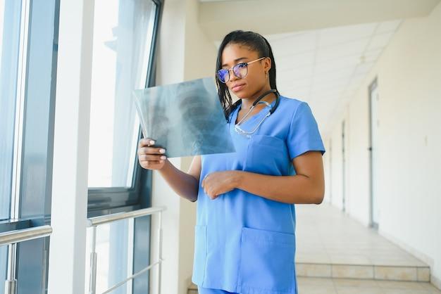 Médico africano examinando o raio-x de um paciente no hospital