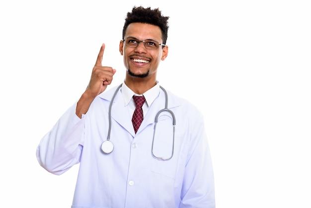 Médico africano feliz e pensativo, sorrindo enquanto aponta o dedo para cima